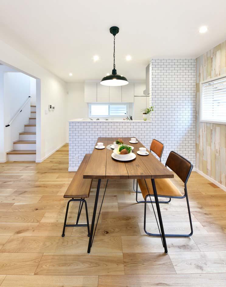 キッチンとダイニングのあいだの壁には白いタイルを施し、カフェ風のお洒落な空間に仕上がった。
