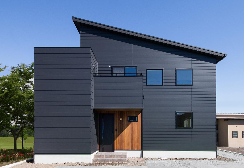 静鉄ホームズ【インテリア、デザイン住宅、間取り】ダークな色のガルバリウムに、玄関まわりにはレッドシダーの木板を張ってアクセント。片流れ屋根のシャープなシルエットがカッコよさを引き立たせる。