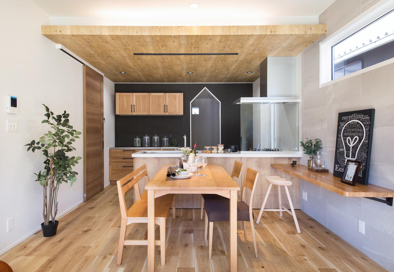 静鉄ホームズ【インテリア、デザイン住宅、間取り】天井間接照明を採用したダイニングキッチン。ナラ樫の床材と色合いを合わせたアクセントの天井クロスや建具が、カッコよさの中にナチュラルな雰囲気を醸し出している。