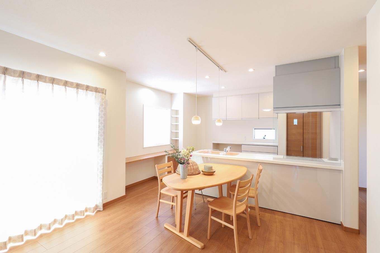 遠鉄ホーム【デザイン住宅、間取り、ガレージ】対面キッチンは、家事をしながらリビングやダイニングにいる家族との会話を楽しむことができる。スペースの広さを活かし、水回りとの回遊動線を作った