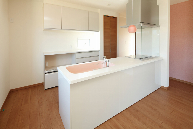 遠鉄ホーム【デザイン住宅、間取り、ガレージ】奥さまの料理タイムが楽しくなる、かわいい色使いのキッチン。コンロの前に油はねを防ぐガラスパネルを採用した
