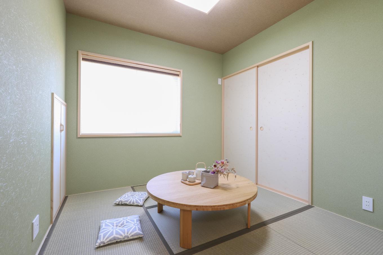 遠鉄ホーム【デザイン住宅、間取り、ガレージ】落ち着いた色合いのグリーンで統一した和室。襖を開放すればリビングの続き間として広く活用できる。階段下収納はおもちゃ入れに便利