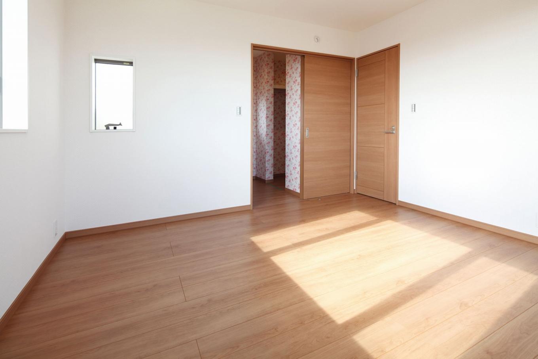遠鉄ホーム【デザイン住宅、間取り、ガレージ】8畳の主寝室に4畳のウォークインクローゼットを設置。棚とパイプハンガーを採用し、使い勝手も抜群。花柄のクロスで華やかさを演出