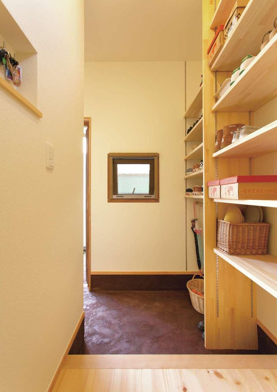 土間玄関はお客さん用と、収納棚を設えた家族用に分けた。庭で採れた野菜の保管場所としても便利