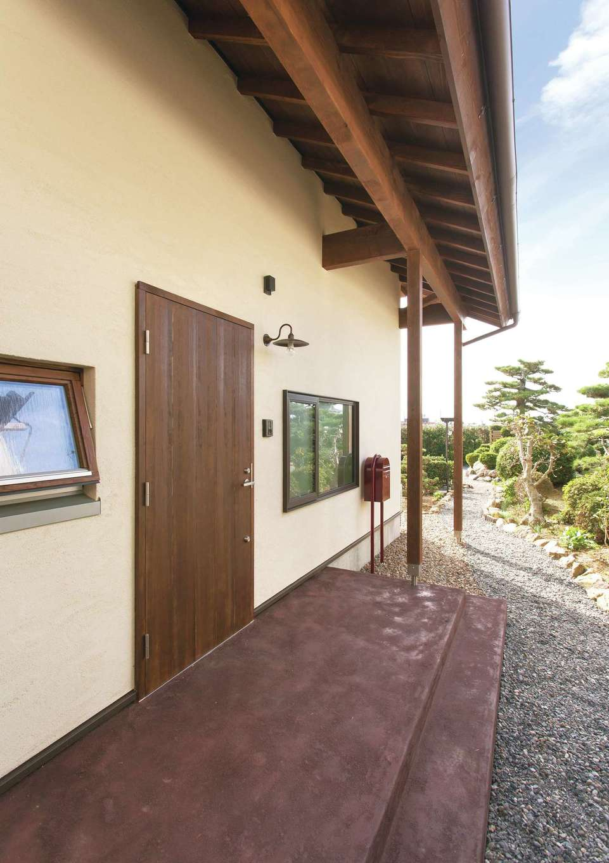 個性を演出できるカラーモルタルの玄関ポーチと木の玄関扉が塗り壁に映える