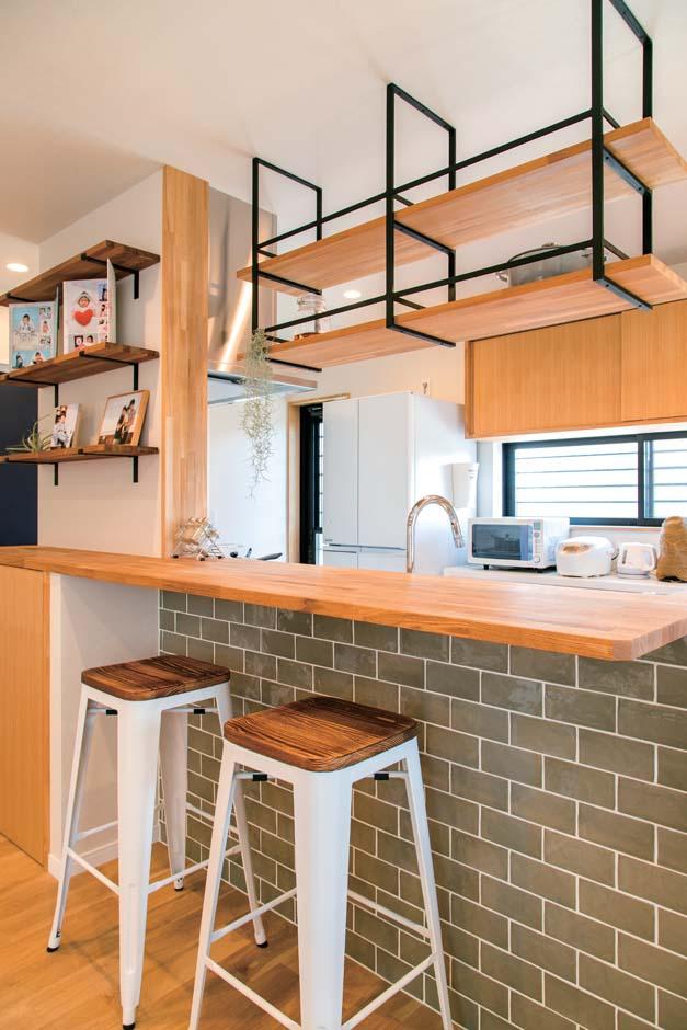 仲田工務店【デザイン住宅、子育て、間取り】タイル壁に木の天板のカウンター、木とアイアンの吊り棚、家族写真を飾る棚など、奥さまの要望を形にしたキッチン。ぐるぐる回れるレイアウトも気に入っているそう