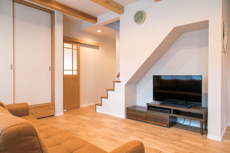 仲田工務店【デザイン住宅、子育て、間取り】階段下のニッチをテレビコーナーに活用。階段の壁は途中からとし、視線が奥まで抜ける。建具もすべて職人の手作り