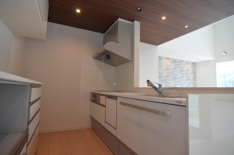 キッチンの天井を木目にしたことで白い空間がグッと引き締まった