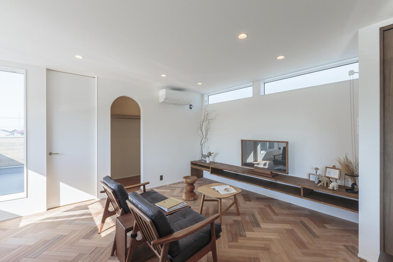 ARRCH アーチ【デザイン住宅、趣味、建築家】ヘリンボーンの床と造作のTV台がベストマッチなリビング。TV台はPCスペースとしても使えるように幅をワイドにしたことで、多機能なカウンターとして活躍。出入口をR型にしたファミリークローゼットはリビングからのアクセスにこだわり、使い勝手を重視