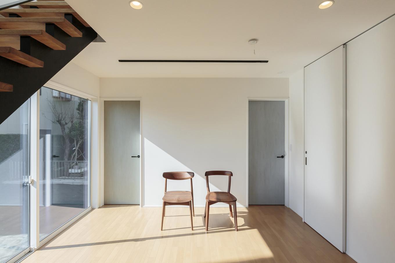 ARRCH アーチ【デザイン住宅、趣味、建築家】玄関を入って家族が必ず通る位置に設けた奥さまのワークスペース。趣味の革細工を楽しむ工房としての機能と、水回りや各個室への通路としての機能を併せ持つ。2つ並んだドアの先は子ども部屋。右手の白い扉の先には洗面・浴室がある