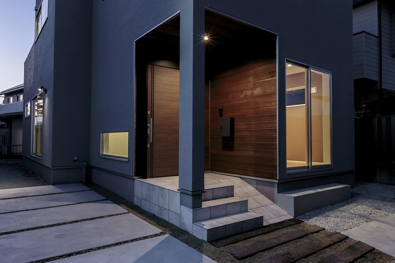 ARRCH アーチ【デザイン住宅、趣味、建築家】玄関ポーチの外壁は無垢板張りに。塗り壁の外壁と調和し、重厚感と温かみのある雰囲気を演出。自転車やカートを土間に上げやすいようにスロープも設けてある