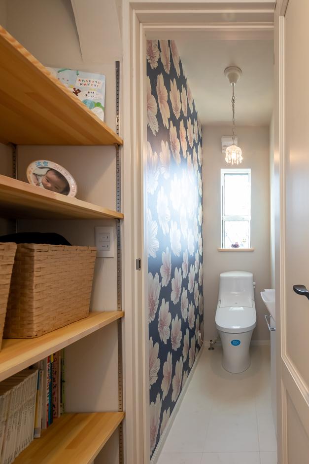 今井建設【子育て、自然素材、間取り】回遊動線上にあるトイレと収納。奥さまがセレクトしたトイレのアクセントクロスは、完成見学会で来場者から大人気だったそう。トイレの前の収納はお子さまのおもちゃや絵本などを隠してしまえるので、リビングはいつもスッキリ・キレイをキープできる