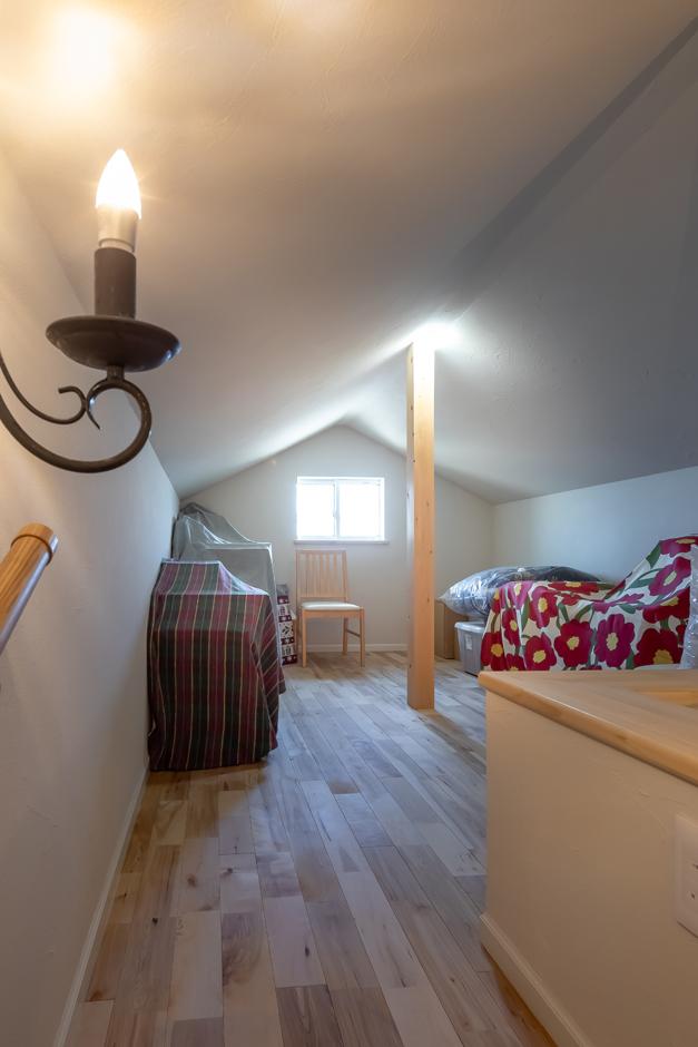 今井建設【子育て、自然素材、間取り】小屋裏の納戸も居室と同様に塗り壁と無垢の床で仕上げてある。三角屋根と自然素材とキャンドル風のシーリング照明で、おとぎ話に出てくる隠れ家のように素敵な空間が実現