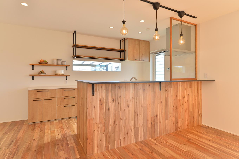 ARRCH アーチ【デザイン住宅、子育て、建築家】室内全体に目が届く「見渡しキッチン」。腰壁を床と動勢にし、一体感を演出。カップボードは吊棚や固定棚と窓を組み合わせ、見映えのいい収納空間を実現