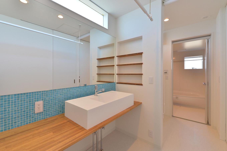 ARRCH アーチ【デザイン住宅、子育て、建築家】シンプルなデザインを極めた洗面スペース。洗面カウンターは幅が約2mあり、軽作業に便利。幅広なミラーが空間をいっそう広く感じさせる。アクセントのモザイクタイルには鮮やかな水色をセレクトし、さわやかに演出