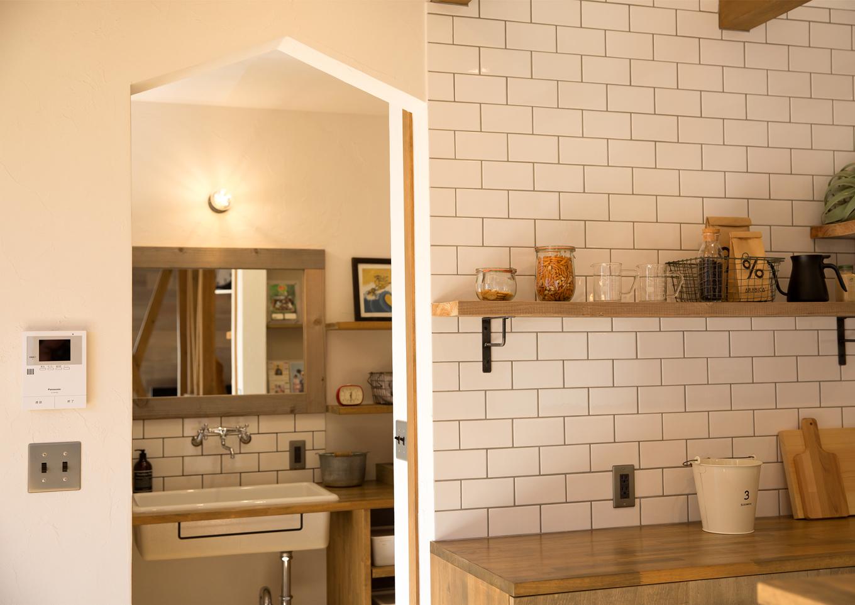 キッチンのサブウェイタイルと、洗面脱衣所の壁がリンクするデザイン。木、珪藻土の塗り壁、アイアンなど、異素材が組み合わさるバランスが絶妙だ。三角屋根の家の開口もセンスの良さを感じさせる