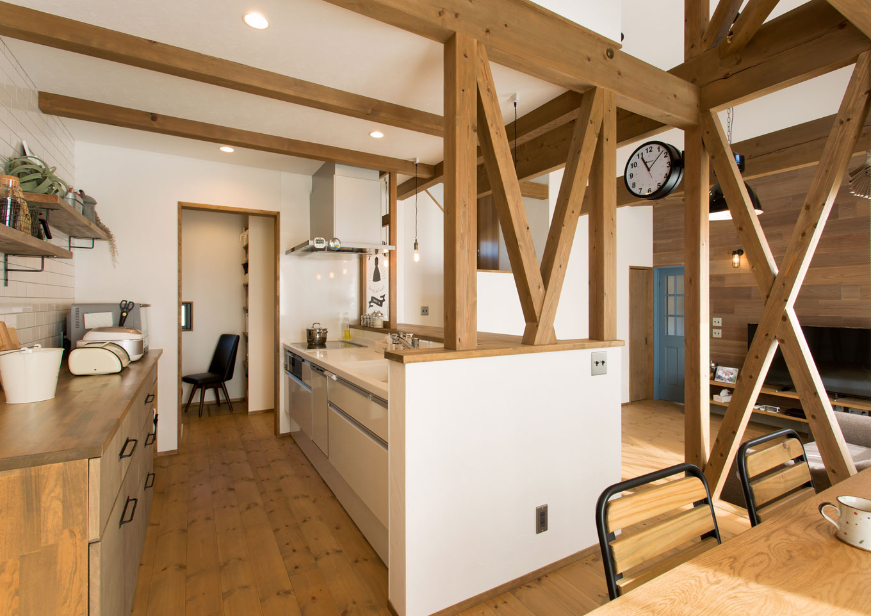 造作したキッチン収納は使い勝手が良く、見える部分はすっきりと物がない。奥にはパントリーも設け、食材棚とパソコンデスクを用意