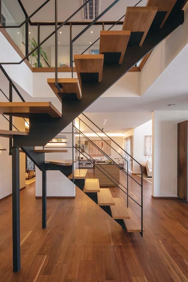 橋本組 ~つむぐ家~【藤枝市高洲1-5-29・モデルハウス】壁側に置くことの多い階段をあえて玄関ホールの中央に据え、デザイン性の高いオープン階段に。玄関を入って正面にあるため視覚的なインパクトがあるとともに、周囲を自由に回遊でき、リビング、キッチン、洗面、和室のどこからもアクセスしやすい