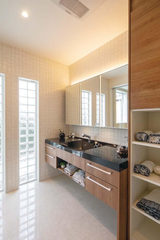 橋本組 ~つむぐ家~【藤枝市高洲1-5-29・モデルハウス】1階洗面室は壁側の間接照明に加えて、鏡と鏡の間に顔を均一に照らすLED照明をプラス。縦型のため影ができにくく、スキンケアやメイクがしやすい。窓の替わりにガラスブロックを入れて明るさだけでなくデザイン性もアップ