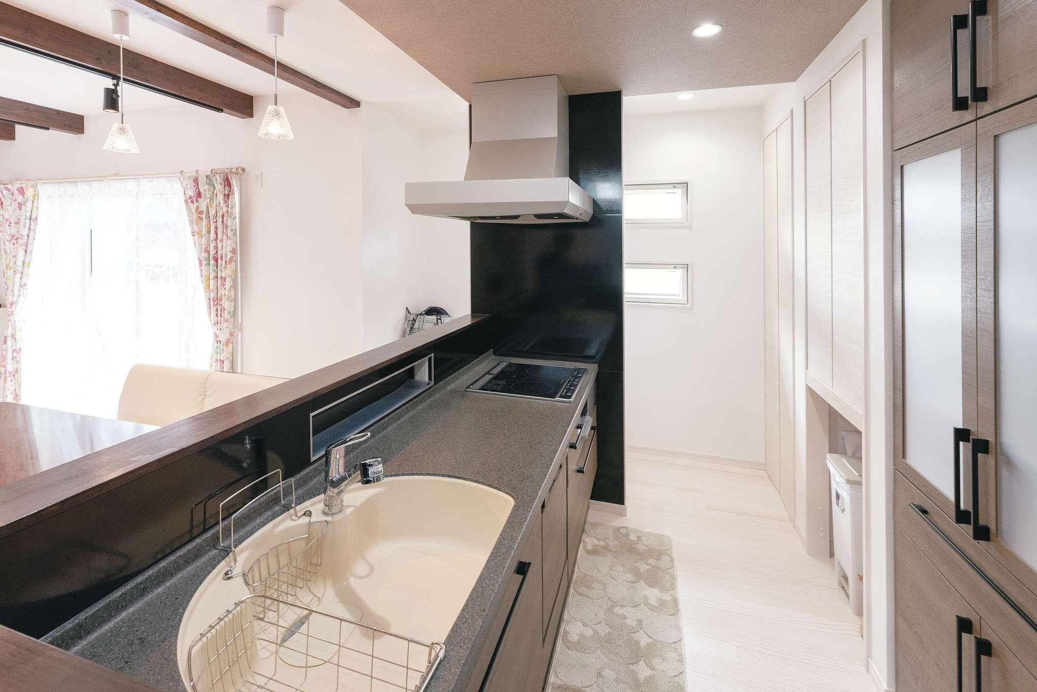 R+house沼津・伊東(HOUSE PLAN)【子育て、収納力、間取り】黒いワークトップがスタイリッシュなキッチン。リビング側の立ち上がり部分に調味料を置くスペースを確保した。キッチンの奥に余白を作り、回遊できる動線が便利