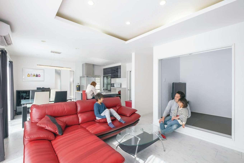 アフターホーム【デザイン住宅、間取り、インテリア】モノトーンを基調にしたNさん夫妻こだわりのリビング。折り上げ天井が空間を広く豪華に見せてくれる。『アフターホーム』からの提案で、玄関ホールとリビングを結ぶ廊下とは別に、キッチン背面にドアを設置。洗面・階段・玄関に直接アクセスできるようにした。炊事と洗濯を並行して行うことができ、LDKへの出入りもここを通ることが多いそう。奥さま大満足の動線だ