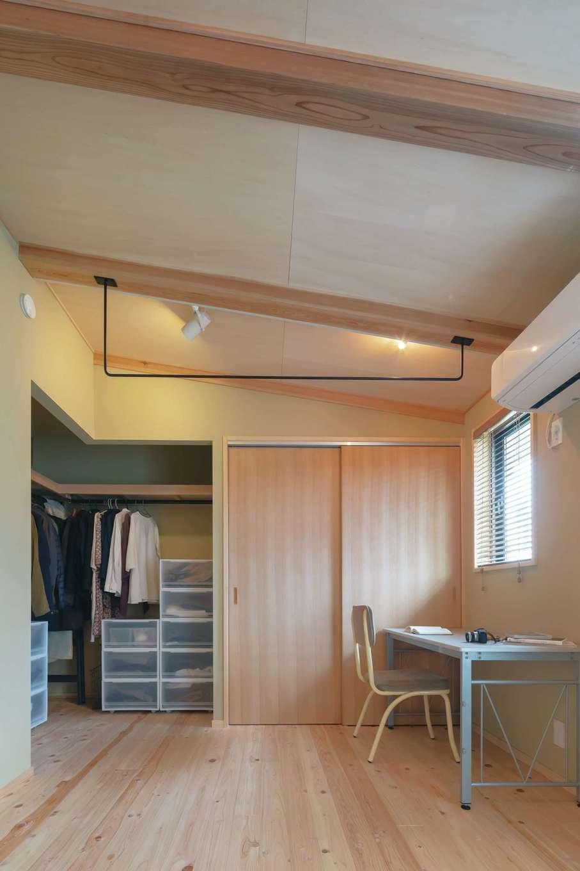 フジモクの家(富士木材)【子育て、自然素材、間取り】勾配天井で実際よりも広く感じられる主寝室。『フジモク』が造作したアイアンの部屋干し用ポールも大活躍