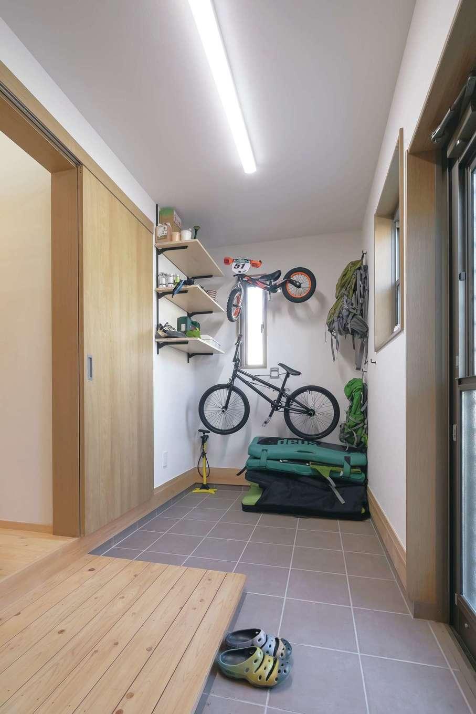 山登り、クライミング、自転車とアウトドア大好き家族のために、グッズをカッコよく見せる土間収納を確保。外からも出入りできる