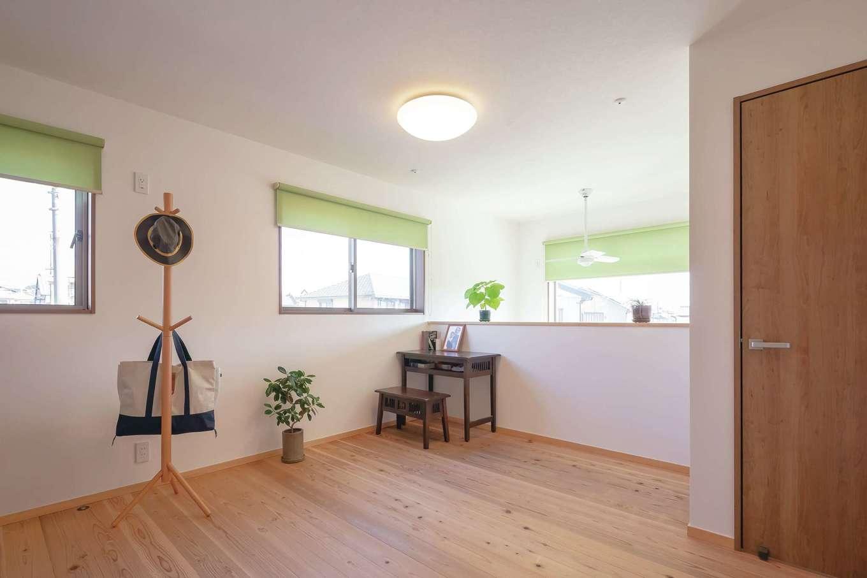 吹抜けに面した2階フリースペースは将来的に間仕切りも可能。やや柔らかい肌触りの床は天竜杉。グリーンのカーテンでより爽やかな空間を演出した。ここから子ども部屋、主寝室へとぐるぐると回遊できる動線になっている