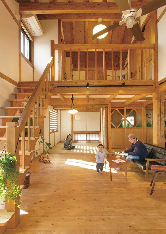 サイエンスホーム【デザイン住宅、自然素材、平屋】切妻屋根の勾配天井を活かし、平屋とは思えないほどの開放感が生まれた。奥さまがデザインした、色ガラス入りの建具が空間のアクセントに