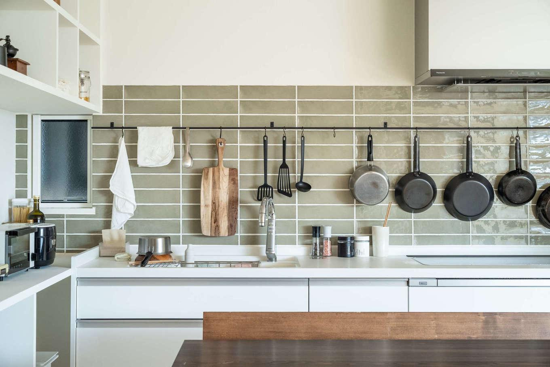 キッシュ『あの家』【デザイン住宅、趣味、インテリア】事務所スペースがある1階から階段を上ると、2階の生活スペースにたどり着く。キッチンのグレータイルは、調理道具を際立てる「見せる収納」に一役買っている