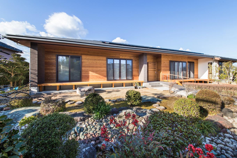 広大な敷地に建つ延床約42坪の平屋建て。東西に長く構え、全室南向きで明るく開放的な空間を実現。無垢板張りの外壁が庭の緑と絶妙に調和している