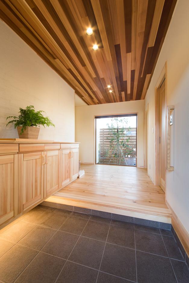 『瀧口建設』の提案で、玄関の天井にもレッドシダーを用いたことで、いっそう洗練された空間に。正面にはピクチャーウィンドを設け、北側の庭の四季を楽しめるようにした