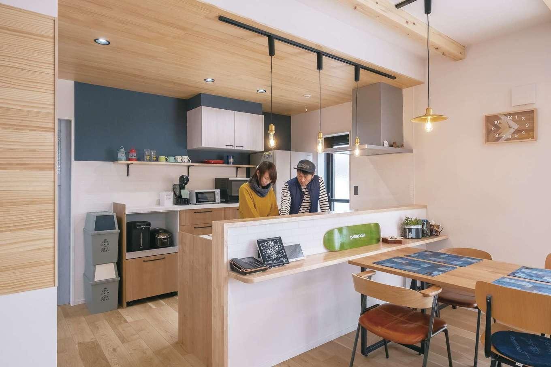 小玉建設【デザイン住宅、子育て、間取り】キッチンの天井にはパイン材を用いた。背面のクロスは色を変えてアクセントに。日常使いの食器類は引き出し収納の中に。オープンシェルフはインテリアも兼ねた見せる収納を意識している