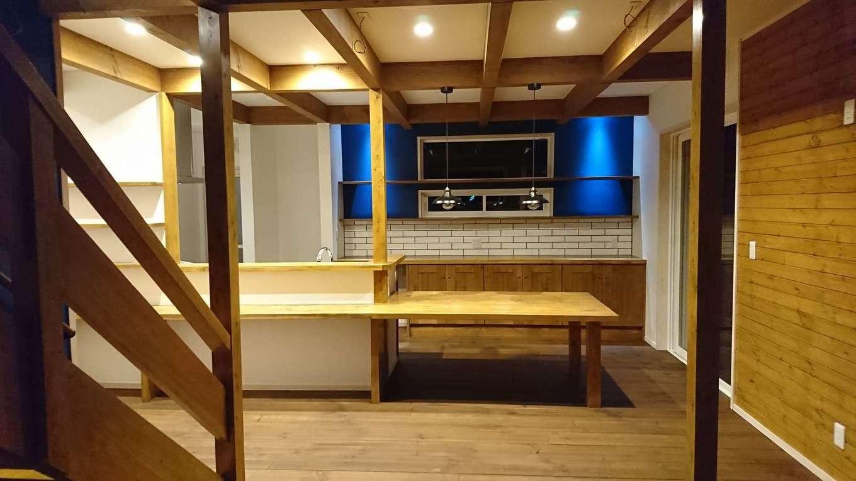 TDホーム静岡西 ウエストンホームズ【デザイン住宅、自然素材、間取り】カフェスタイルのキッチンは、ダイニングテーブルを接続させたことで、配膳やお片づけの時間を短縮でき、家事効率が大幅にアップ。バックヤードの青いクロスとサブウェイタイルの間に隙間を設け、そこに間接照明の灯りが落ちるように工夫した