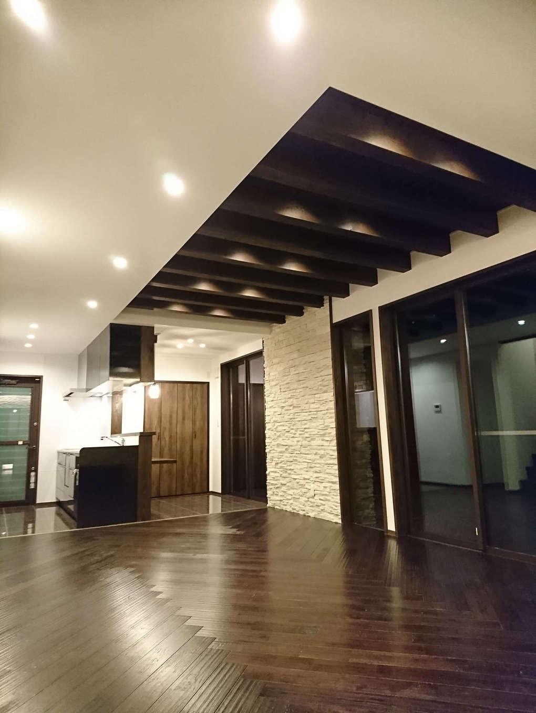 TDホーム静岡西 ウエストンホームズ【デザイン住宅、夫婦で暮らす、間取り】リゾートホテルを思わせる開放感あふれるLDK。ヘリンボーン張りのクリの床が目線を奥へ奥へと誘う。リズミカルに配した意匠梁がモダンな空間をより引き立てる