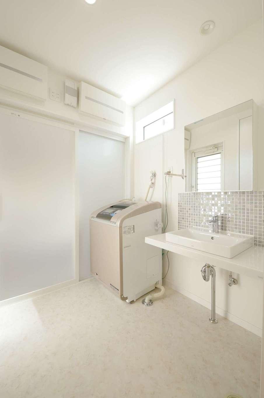 洗面台の下に収納棚を付けないことで開放感が生まれた。ワイドな鏡とタイルがアクセントに