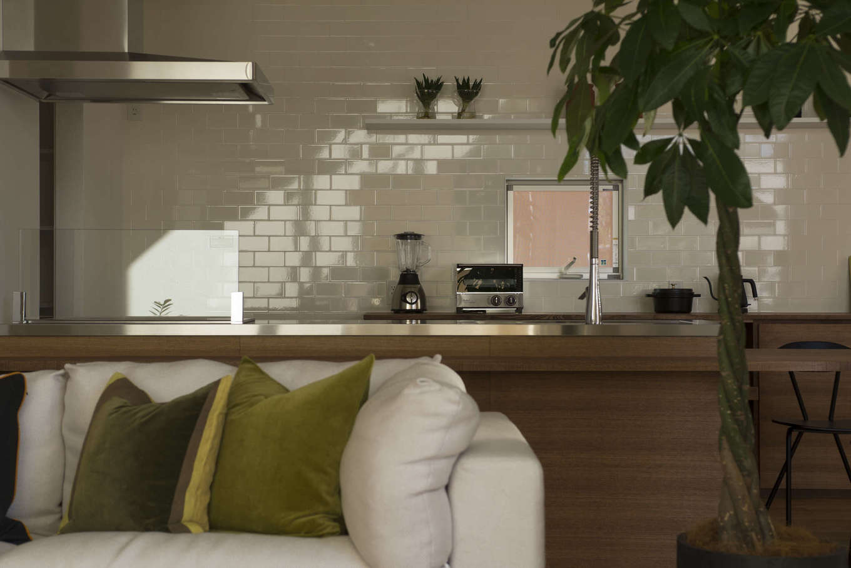 キッチンは奥さまが主役のステージ。壁一面に白いタイルを貼り、奥さまがいっそう輝く空間に。ソファに座ったご主人が何気なくふりむくと、そこに素敵な笑顔がある