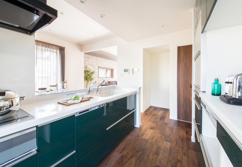 静鉄ホームズ【デザイン住宅、省エネ、インテリア】鏡面仕上げのダークグリーンな扉のシステムキッチン。カップボードのほかにパントリーもあるため、いつでもスッキリとしたキッチンが目指せる