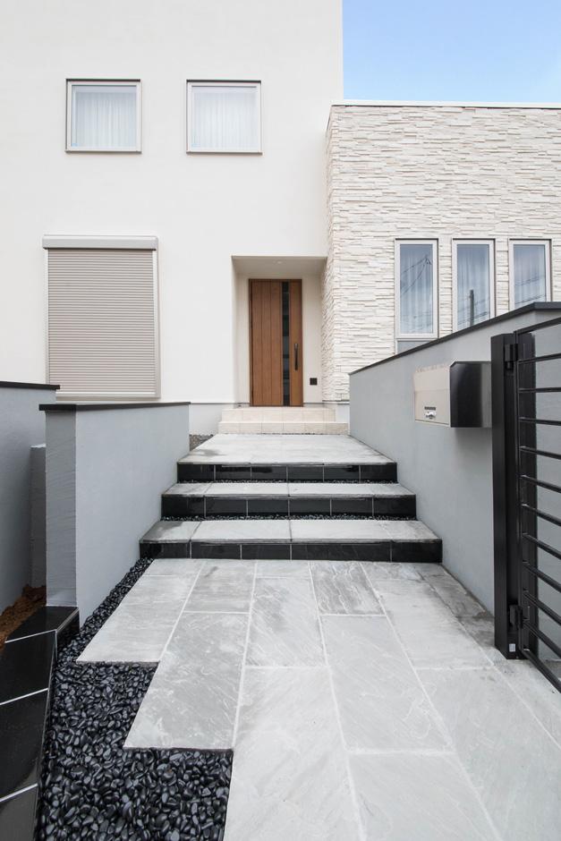 静鉄ホームズ【デザイン住宅、省エネ、インテリア】白い建物とのコントラストを考えてデザインされたアプローチ。黒い石やタイルで引き締めている