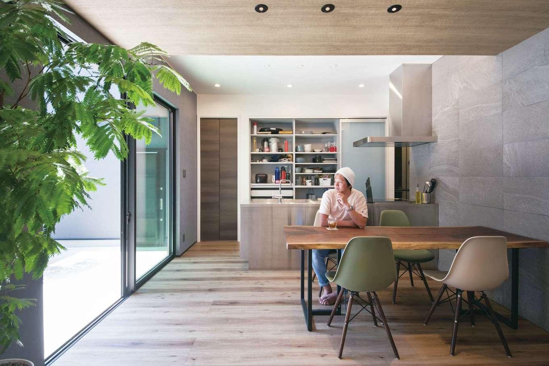 静鉄ホームズ【デザイン住宅、間取り、インテリア】中庭とリビングがフラットにつながる開放的な室内。奥さまの夢を叶えたオールステンレスのキッチンがインテリアの主役に。タイルの壁と突き板の天井の組み合わせが都会派の暮らしを演出