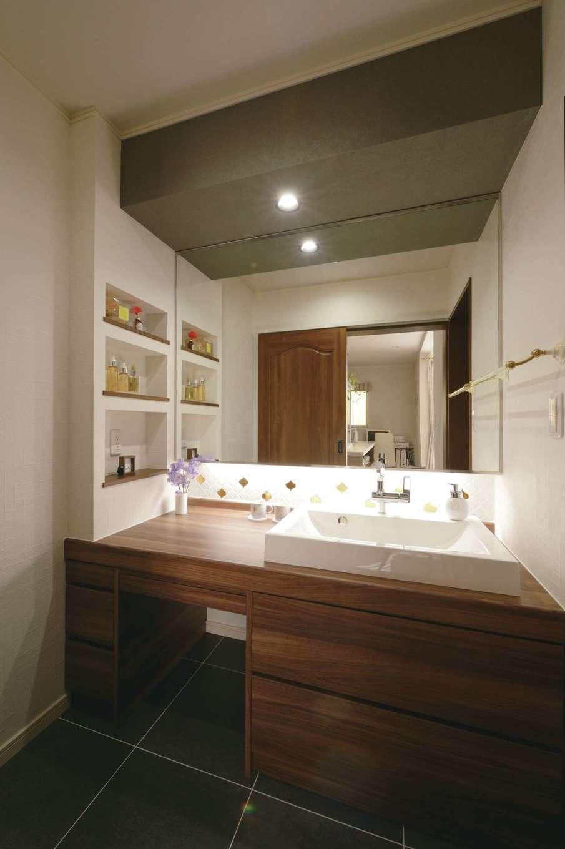 朝日住宅【デザイン住宅、間取り、インテリア】スペースを広くとったフルオーダーの洗面所は、濃い色調でシックにデザイン。来客時の使用を考慮し、脱衣室と仕切って使えるようにした