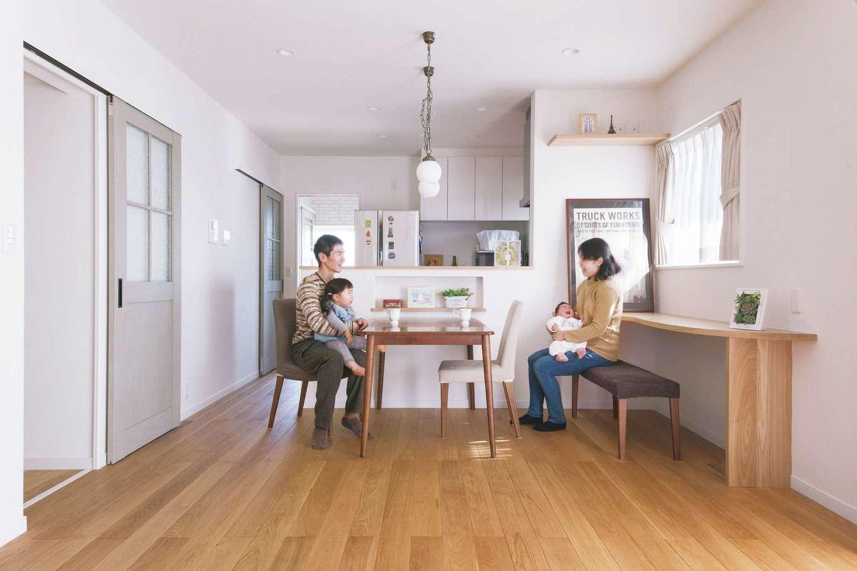 四季彩ひだまり工房 高田工務店【子育て、収納力、間取り】無垢のオークの床と、漆喰の塗り壁が優しい色合いを醸し出すLDK。ニュアンスグレーのドア、雑貨照明などのコーディネートもセンスが良く、『四季彩ひだまり工房 高田工務店』が得意とする木のぬくもり漂う雰囲気が心地いい。長期優良住宅の高い性能により、耐震等級3と高気密・高断熱の省エネな暮らしを実現しただけでなく、太陽光発電の売電量で消費電力をまかなえるゼロ・エネルギー住宅というのも心強い!