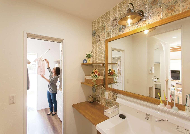ほっと住まいる【自然素材、間取り、インテリア】モザイクタイルが素敵な水回り。ファミリークローゼット兼部屋干しスペースを脱衣室と洗面室の延長上に配置することで、「入浴・洗濯・干す・しまう」がごく短い直線上で完結する。ファミリークローゼットは庭にも直結しているので、天気のよい日は外干しもOK。奥まった場所にあるため、生活感を隠せるという利点も