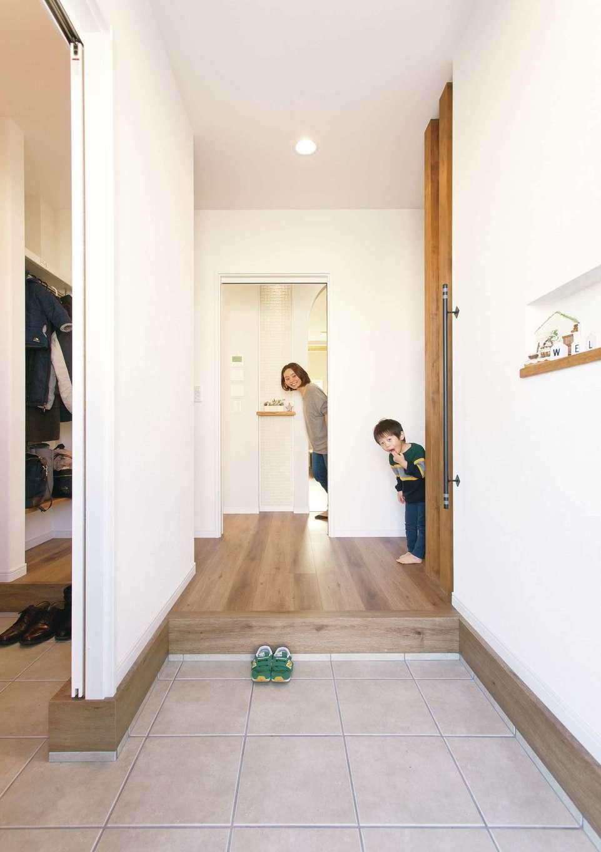 ほっと住まいる【自然素材、間取り、インテリア】玄関ホールでお客さんをお出迎え。奥さまのいるキッチンからも、出入りの気配が感じられる。向かって右側はトイレスペース