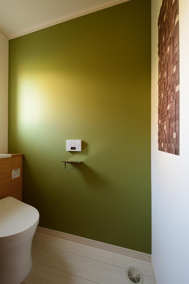 Yamaguchi Design 【デザイン住宅、収納力、間取り】デザイナーの奥さまらしいセンスが光る、オリーブ色のクロスを貼ったトイレ。消臭効果の高いエコカラットも採用。「eco-i熱交換型換気システム」により、家中どこにいても温度差がないので、冬の深夜にトイレに入ってもヒートショックの心配がない