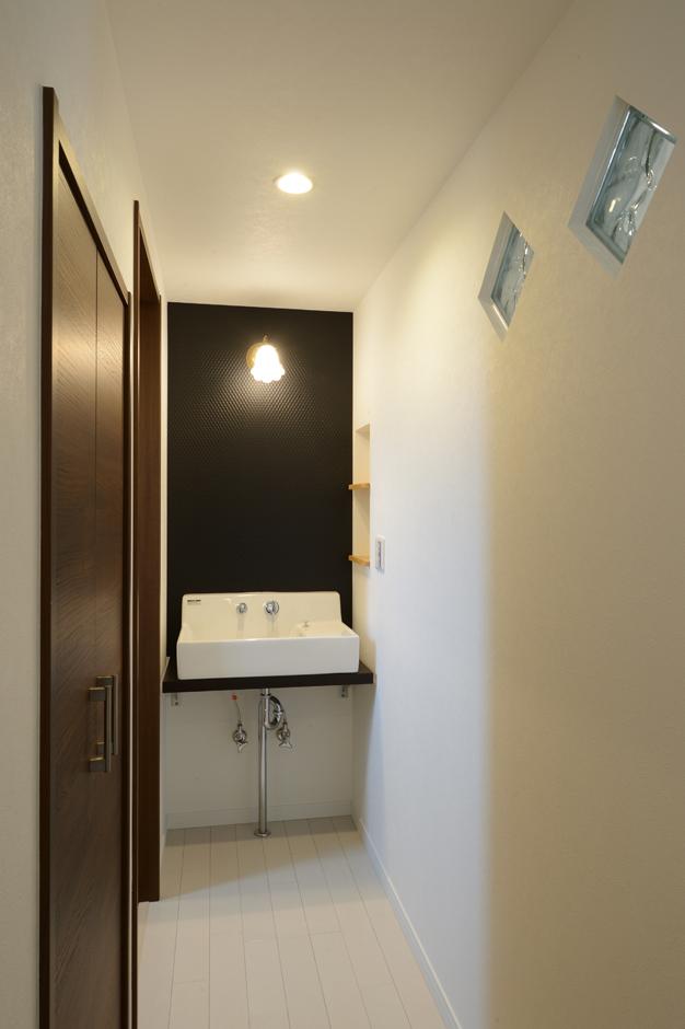 洗面台とトイレが暗くならないよう、廊下の壁にガラスブロックを設け、LDKから明かりをとるように工夫した