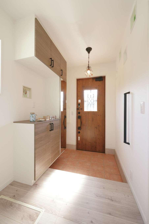 ほっと住まいる|玄関ホールと1階トイレは増築。ペンダントライト、造作のニッチ、アイアンがシンプルな空間のアクセントになっている