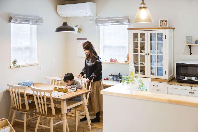 今井建設【自然素材、間取り、インテリア】キッチンの真横にダイニングテーブルを置くことで、奥さまの家事時間を短縮。子どもはいつもママに見守られて、安心して勉強やお絵描きができる。奥には家事コーナーも造作。照明器具のセレクトもすてき