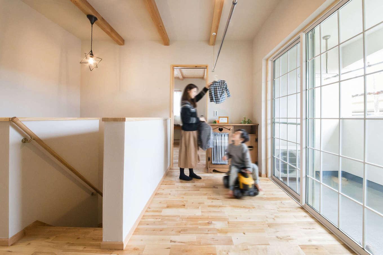 室内干しコーナーを設けた2階のフリースペース。呼吸する無垢材と塗り壁の相乗効果で、洗濯物がよく乾くので生乾きの不快な臭いがしない。格子入りの大きな掃出し窓がおしゃれで洗練された雰囲気を演出