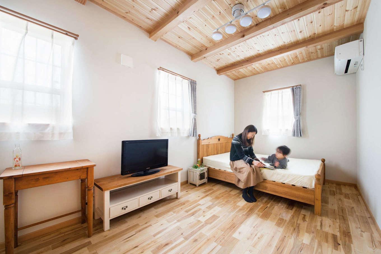 梁を現しにしたパイン材の勾配天井に癒される主寝室。レースのカーテンと上げ下げ窓の組み合わせが合う家づくりも『今井建設』の特徴。ウォークインクローゼットを夫婦別々につくり、お出かけ時のストレスも解消